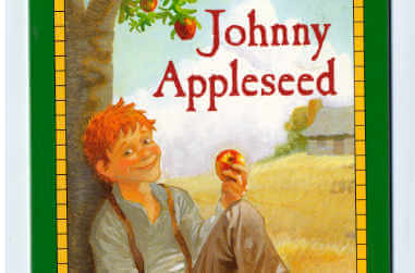 A young man eating an apple while sitting up against an apple tree - thumbnail
